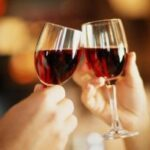 COUPLE MAKING A TOAST IN WINE [CLOSE-UP OF HANDS AND GLASSES]